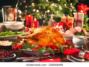Weihnachtsputenessen. Backturne mit roten Beeren und Salbei vor Weihnachtsbaum und brennenden Kerzen