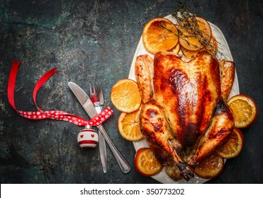 Christmas turkey with fork,knife and festive decoration on dark rustic background,top view