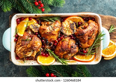 Christmas turkey legs baked with cranberries, orange and rosemary. Delicious festive dish for Christmas time. Top view,  flat lay