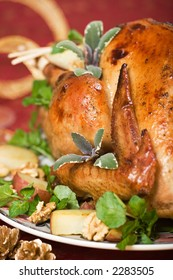 Christmas turkey served with herbs, baked potatoes and walnuts on holiday table