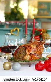 Christmas turkey stuffed with rice on a christmas table, candles, wine glasses and ornaments around