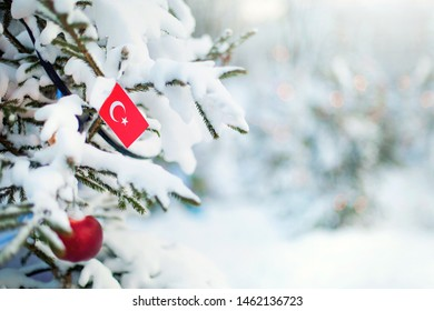 Christmas Turkey. Xmas tree covered with snow, decorations and a flag of Turkey. Snowy forest background in winter. Christmas greeting card.