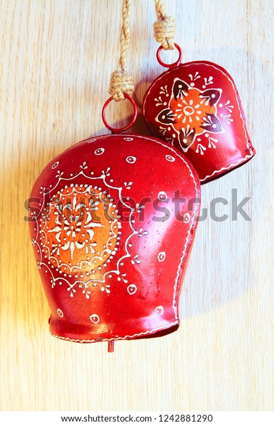 Christmas Tyrolean red metal cowbells with hand drawn ornament on oak wood background.