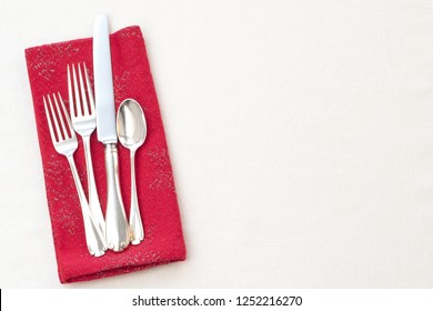 Christmas or Valentine's Day Holiday Place Setting with red napkin, forks, knife, spoon silverware on cream or off white textured table cloth background.  Horizontal flatlay taken from above view