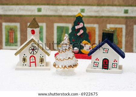 christmas village decorations with falling snow on white base