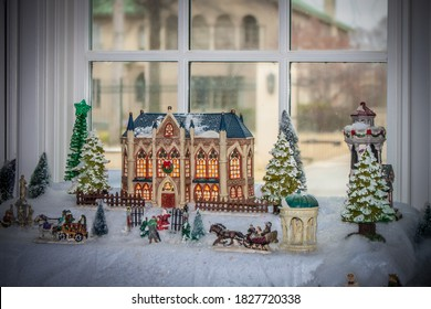 Christmas Village scene with beautiful building  and santa at gate and horses and carrages all in bay window with blurred mansion showing through
