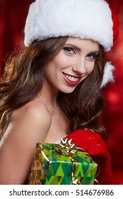 Christmas vintage brunette with gift box, isolated on grey. Fashion in retro style
