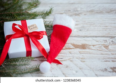 Christmas white box or present with red ribbon for secret santa with santa hat on wooden table