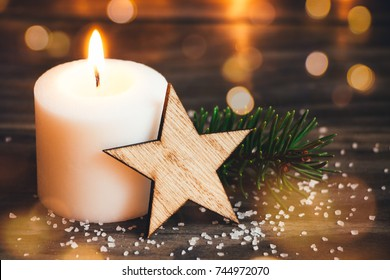 Christmas white candle with a wooden star, fir branch and lights bokeh at the background
