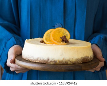 Christmas white orange  cheesecake with mascarpone in hand woman. Festive Christmas food  traditional winter cake