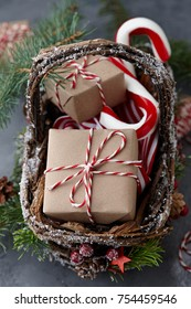 Christmas wicker basket with gifts or present boxes wrapped in kraft paper and candy canes on gray stone background, festive decoration