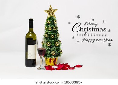 Christmas wine, red rose petals and glass wine with small artificial xmas tree. Greeting message on white. Elegant holiday post digital card. Merry Christmas and Happy new year 2021. Copy space