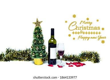 Christmas wine, red rose petals and glass wine with small artificial xmas tree and multi-colored tinsel. Greeting message on white. Template for postcards for Christmas and New Year 2021. Studio shot