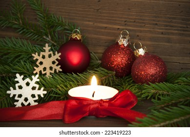 Christmas, Winter or Advent Background with Copy Space in red Colors with a Candle and Winter Decoration on Wood
