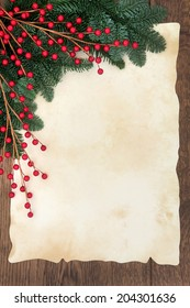 Christmas and winter background border with fir and red ball decorative sprays over old parchment paper and oak wood.