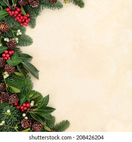 Christmas and winter background border with fir, holly, ivy, mistletoe and pine cones over old parchment paper.