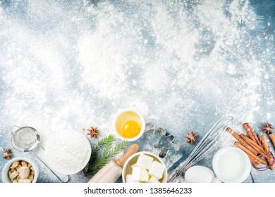 Christmas and winter baking background. Kitchen utensils and ingredients for cooking baking - flour, sugar, eggs, butter, milk, cinnamon sticks, whisk, rolling pin, anise,