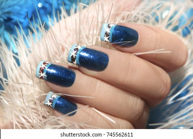Christmas winter blue design French manicure with snowflakes at the end of the nails.