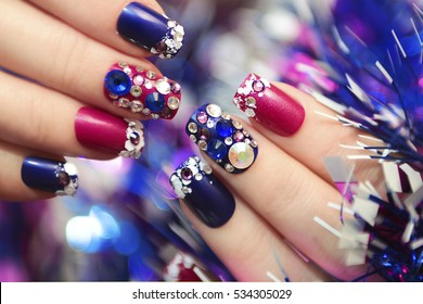 Christmas winter blue manicure with rhinestones of different shapes and sequins in the form of snow on female hand with tinsel.