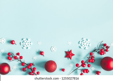 Christmas or winter composition. Frame made of snowflakes, balls and red berries on pastel blue background. Christmas, winter, new year concept. Flat lay, top view, copy space