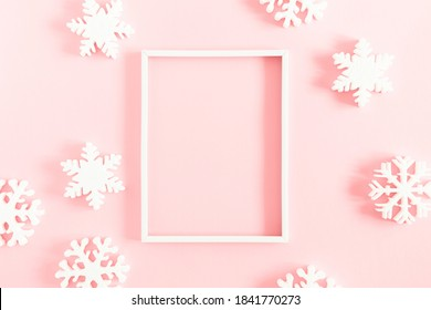 Christmas, winter composition. Xmas decorations, photo frame, snowflakes on pastel pink background. Christmas, New Year, winter concept. Flat lay, top view, copy space