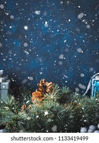 Christmas winter dark background with decorations on blue with green fir tree branches