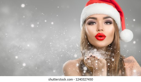 Christmas Winter Fashion Girl blowing snow in Her Hand. Beautiful New Year and Xmas Holiday Makeup. Gift. Beauty Model woman in Santa hat on Holiday Blurred winter Background, sale. Widescreen