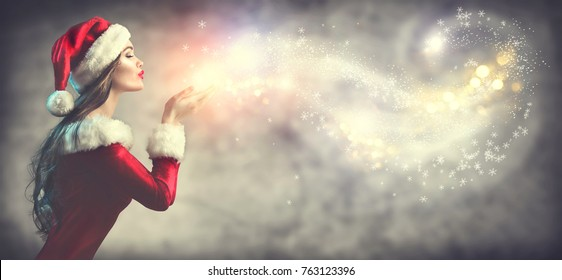 Christmas Winter Fashion Girl blowing  Magic snow in Her Hand. Fairy. Beautiful New Year and Xmas Holiday Makeup. Gift. Beauty Model woman on Holiday Blurred winter Background, sale. Wide angle banner
