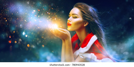 Christmas Winter Fashion Girl blowing  Magic snow in Her Hand. Fairy. Beautiful New Year and Xmas scene. Holiday Hairstyle, Makeup. Gift. Beauty Model woman on Holiday winter Background, sales concept