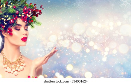 Christmas Winter Girl blowing with Magic snow in Her Hand. Fairy. Beautiful New Year and Xmas Tree Holiday Hairstyle, Makeup. Gift. Beauty Fashion Model woman on Holiday Blurred blue Background, sales