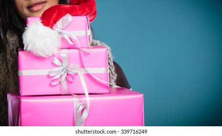 Christmas winter happiness concept. Girl mixed race woman wearing santa helper hat holding stack of presents gift boxes on blue