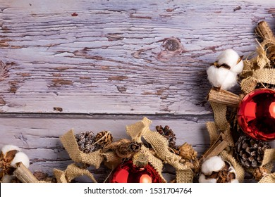 Christmas / Winter Holiday themed rustic background. decorated with pine cones, red ornaments, cotton, and a string of yarn and sticks. Shot from above on a old wooden table. With free space for words