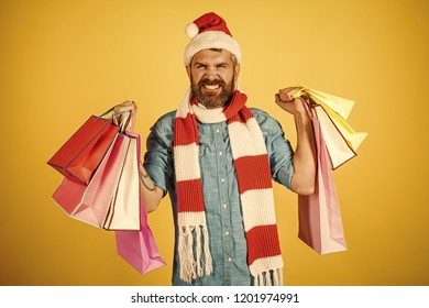 f3523247a9ed8 Christmas winter holidays celebration. Man hold shopping bags on yellow  background. Hipster shopper happy