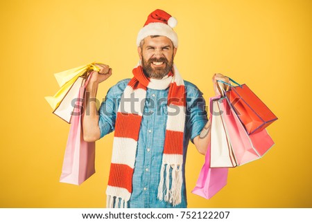 5d7321a420529 Man hold shopping bags on yellow background. Hipster shopper happy smile in santa  hat and scarf. New year