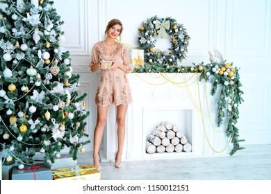 Christmas, winter holidays concept. Beautiful charming woman in evening dress posing in luxurious apartments decorated for Christmas. Beauty, fashion.