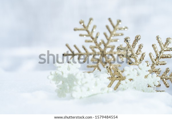 Christmas of  winter - Christmas Snowflakes on snow, Winter holidays concept. White and Golden Snowflakes decorations In Snow Background