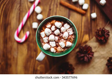 Christmas winter still life : a cup of cocoa with marshmallows sprinkled with chocolate chips , candy, fir cones and cinnamon sticks on a wooden table top view