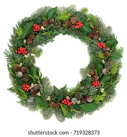 Christmas and winter wreath decoration with holly, mistletoe, juniper fir, blue spruce, cedar, pine cones and ivy leaves on white background.