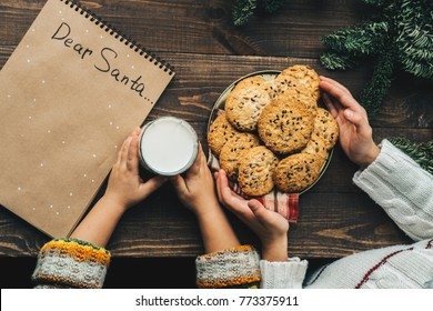 Christmas wish list letter, Children make surprise present for Santa claus milk and oat cookie. Top view and holding hands . Xmas family tradition, Childhood concept