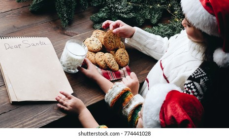 Christmas wish list letter, Children make surprise present for Santa claus milk and oat cookie. Cropped view  and holding hands . Xmas family tradition, Childhood concept.
