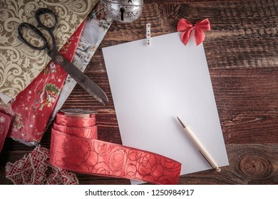 Christmas wish list for Santa. Top-down view on a blank letter on the wooden table.