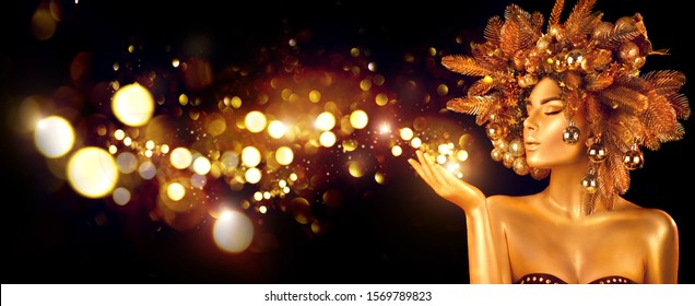 Christmas Wish. Winter Woman with Magic in Her Hand. Beautiful New Year and Christmas Tree Holiday Hairstyle and gold skin Makeup. Gift. Girl in Xmas wreath. Beauty Fashion Model Holiday Background