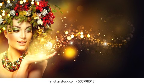 Christmas Wish. Winter Woman with Miracle in Her Hand. Fairy. Beautiful New Year and Christmas Tree Holiday Hairstyle and Makeup. Gift. Magic Girl. Beauty Fashion Model over Holiday Blurred Background