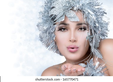 Christmas woman. Beautiful christmas girl with sensual lips sending a kiss. Vogue style model blowing her hand