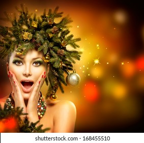 Christmas Woman. Beautiful New Year and Christmas Tree Holiday Hairstyle and Make up. Beauty Girl Portrait. Colorful Makeup, Hair, Nail polish and Accessories. Surprised Woman. Open Mouth, Emotions