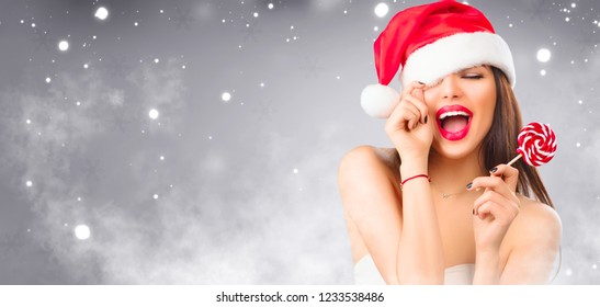 Christmas woman. Beauty model girl in Santa Claus hat with red lips and xmas lollipop candy in her hand. Joy. Surprised expression. Closeup portrait over winter snow wide background with copy space