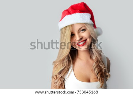 51dfcaec2c5 Christmas Woman. Beauty Model Girl in Santa Hat. Funny Laughing Surprised  Woman Portrait.