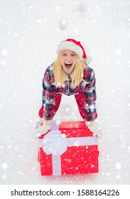 Christmas Woman holding a huge gift box. Woman present red gift box with ribbon bow isolated over white background. Big gift box. Hipster Girl with Christmas gift on snow Winter landscape