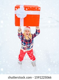Christmas Woman holding a huge gift box - full length. Christmas winter people. Love winter. Happy woman in red dress having fun with big gift box isolated on a white snow background