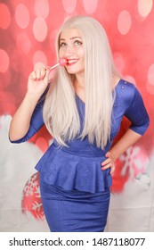 Christmas woman in peplum dress with lollipop candy on red xmas background